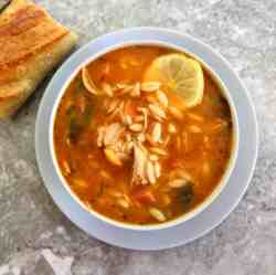 A bowl of orzo soup garnished with a slice of lemon shown with a piece of baguette next to the bowl, on the left hand side.
