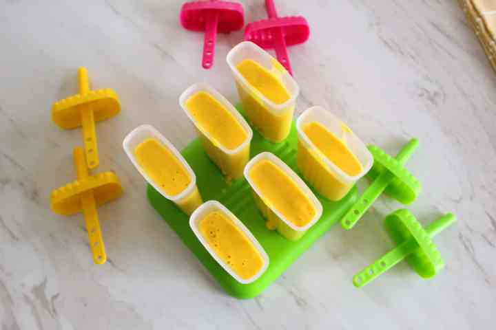 Popsicle molds filled up with the mango blend ready to be frozen.