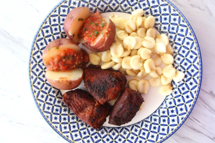 A white and blue plate with pork chicharron, mote, red potatoes and llajua.