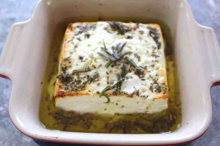 A baking dish showing a freshly baked block of feta cheese in olive oil and covered in herbs.