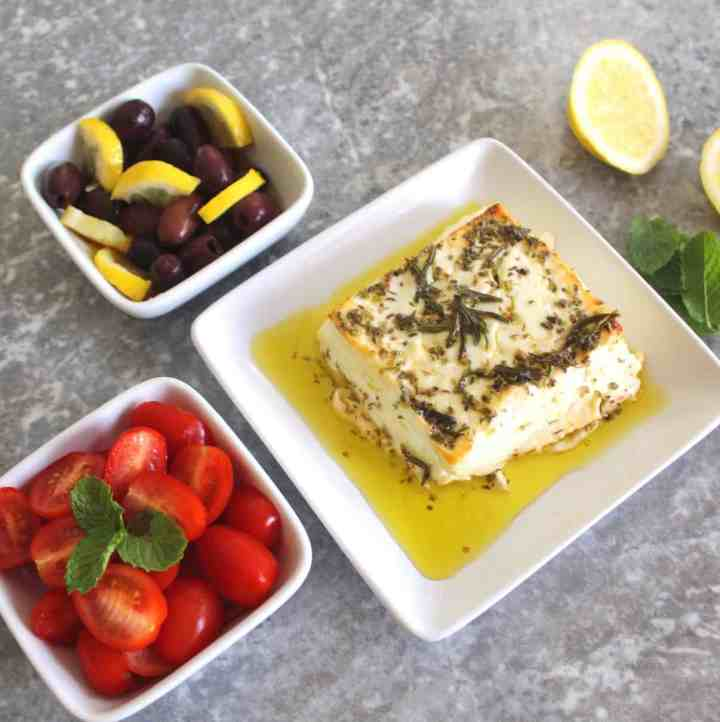 Baked feta cheese in olive oil and herbs shown next to two other sides, olives with lemon and grape tomatoes.