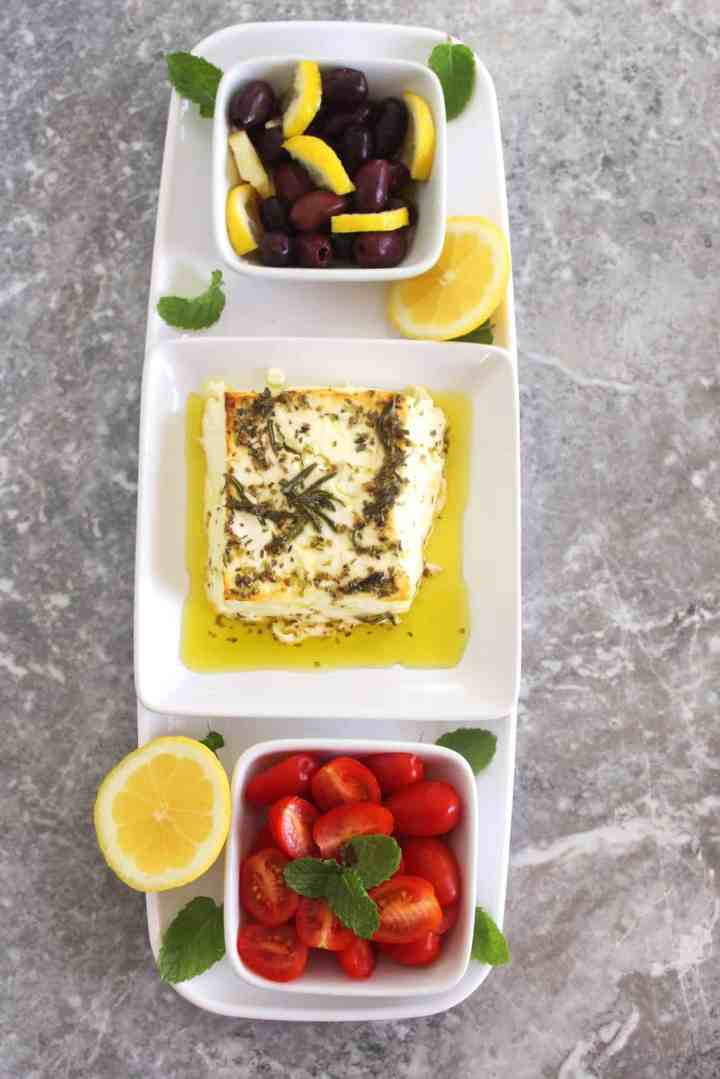 Appetizer tray with 3 separate side dishes: from top to bottom, olives with lemon, baked feta cheese, herbed in olive oil and lastly grape tomatoes with mint.