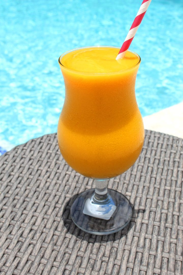 A poolside table with a frozen cocktail on it, ready to be enjoyed. Frozen drink looks tropical.