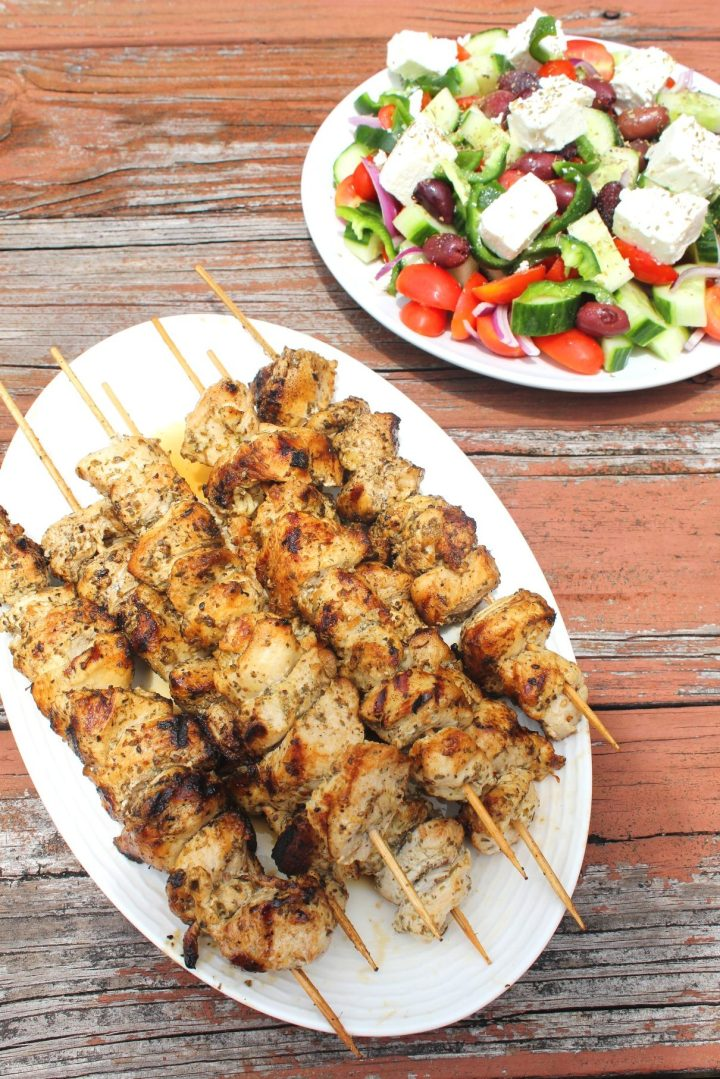 An oval platter of chicken kabobs still in skewers next to a plate of greek salad. Both plates are on a rustic looking wood surface.