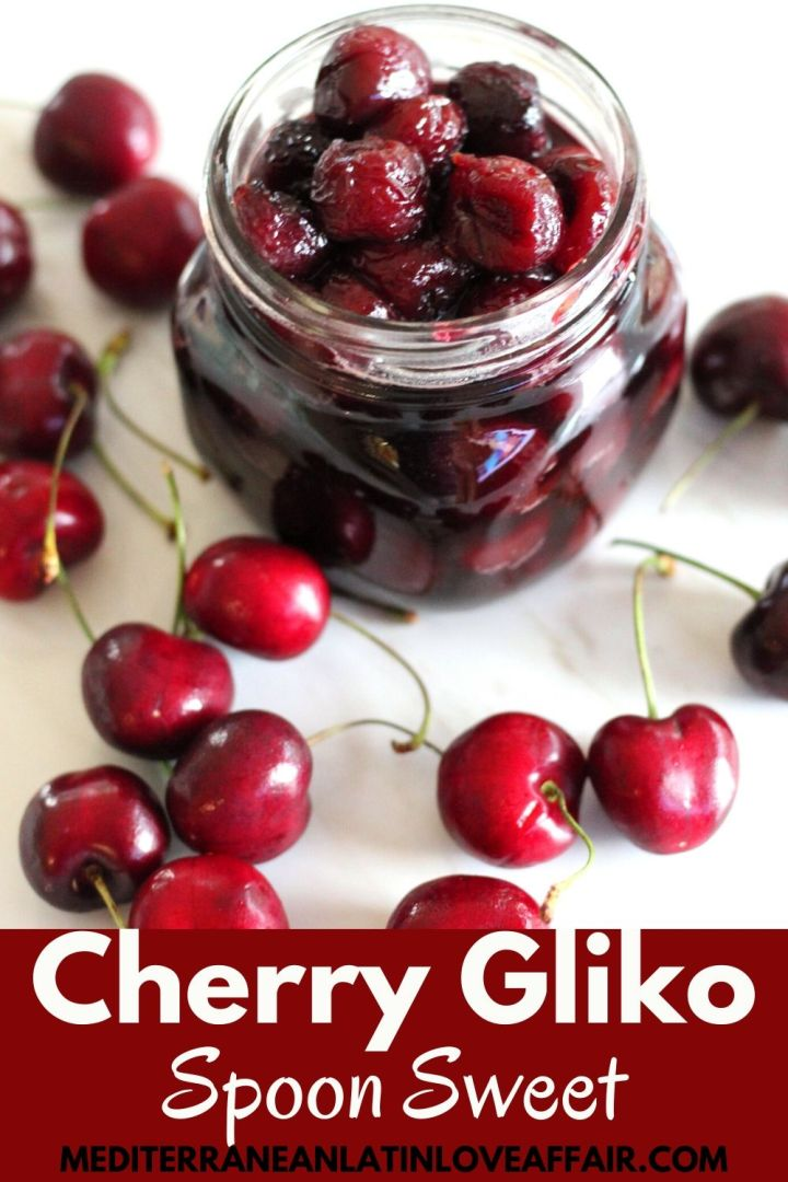 Cherry spoon sweet shown in a jar, surrounded by fresh cherries. Image is prepared specifically for Pinterest because it is shown with a banner that has the title Cherry Gliko across.