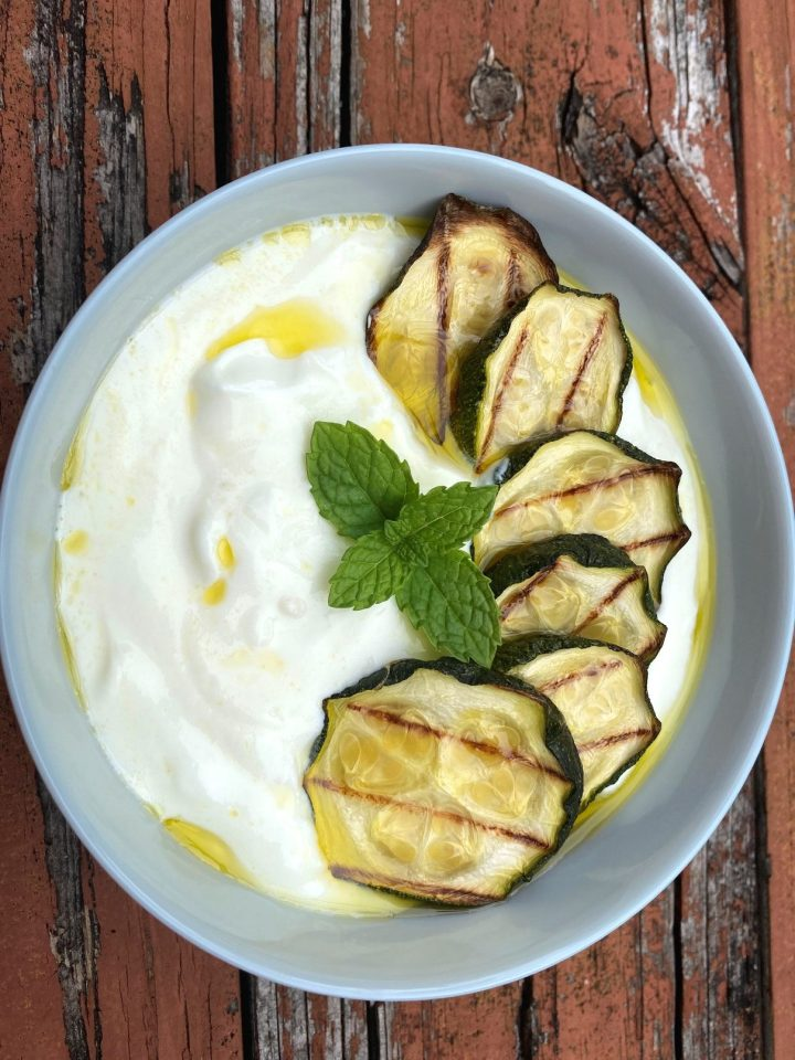 Zucchini Chilled Yogurt Soup - the  yogurt soup in on a bowl placed in a rustic surface. Soup is topped with zucchini slices, mint and olive oil.