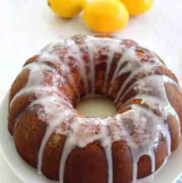 Meyer Lemon bundt cake shown on a round platter with fresh lemons in the background