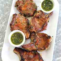 Platter with golden brown, juicy pork chops served with 2 sides of mint chimichurri sauces.
