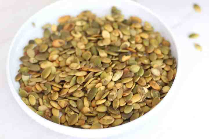 Pumpkin seeds or pepitas on a round plate. These seeds are used as a topping for the soup.