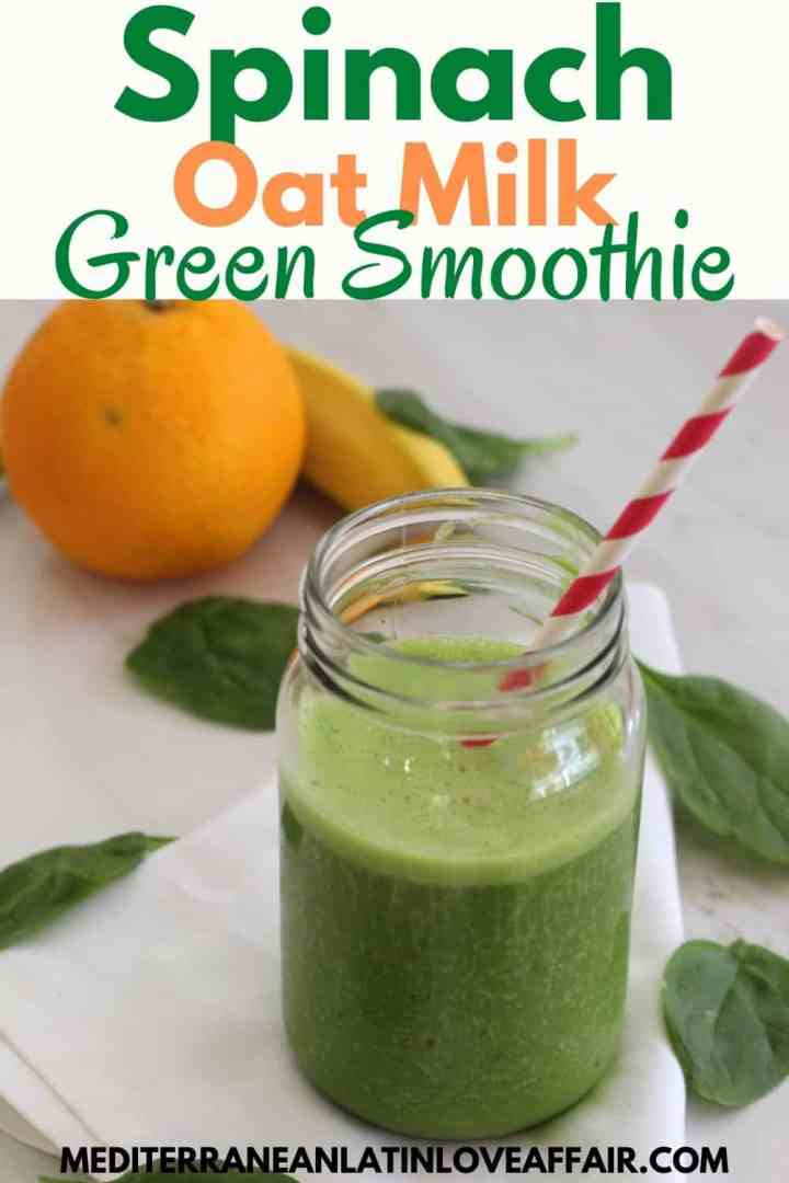A jar with green smoothie over a white napkin. There are spinach leaves, an orange and a banana around the jar.