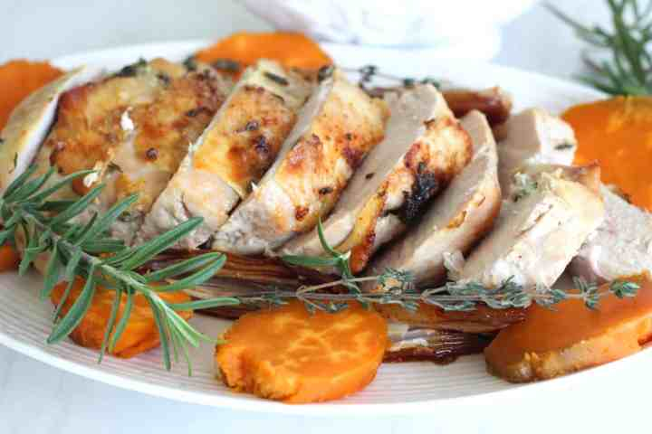 Roasted turkey breast on a platter, accompanied with herbs, sweet potato slices.