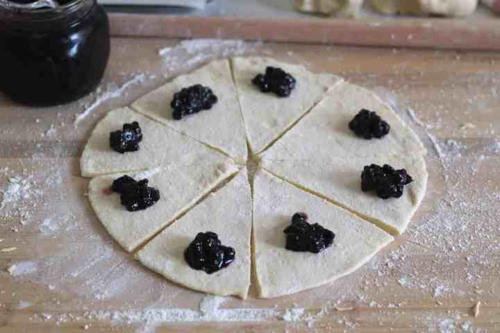 Dough flattened in a circle on a dusted with flour surface. Dough is cut into pizza shape slices, each has a spoon of jam placed in the corner. Dough is ready to roll.