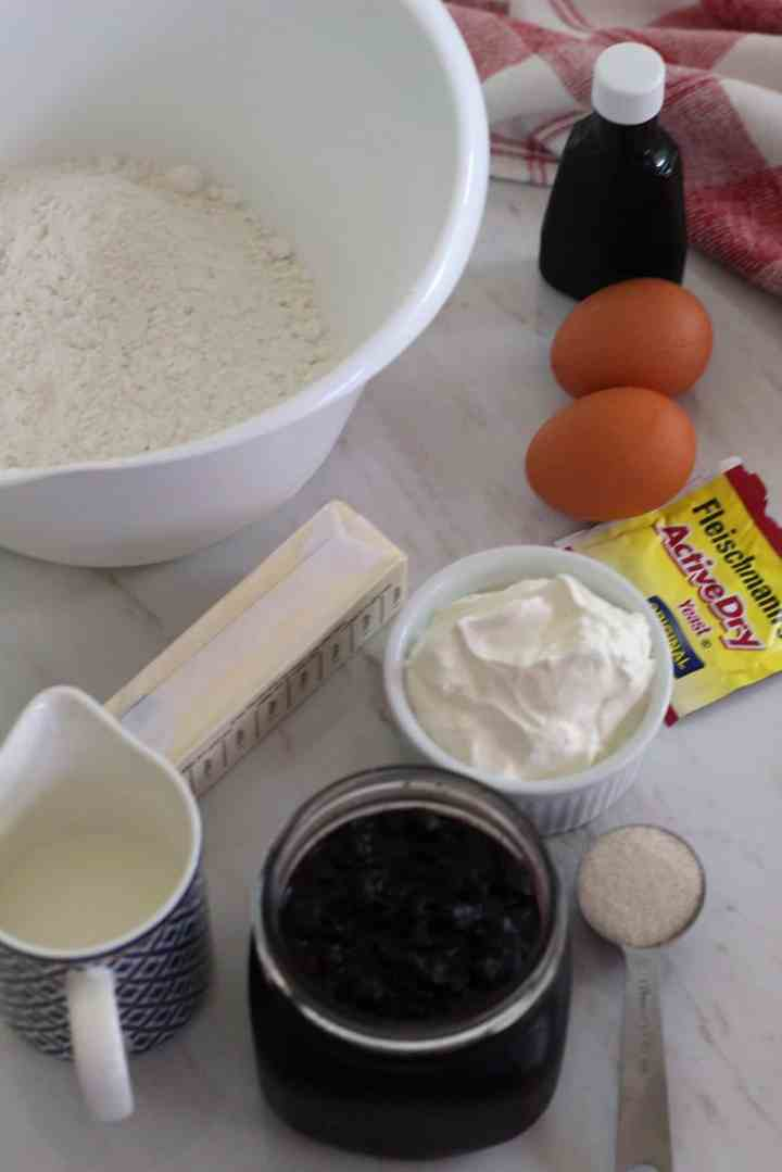 Several ingredients laid out for making the sour cream cookies. Flour, vanilla, eggs, yeast, sour cream, milk, sugar, butter and jam.