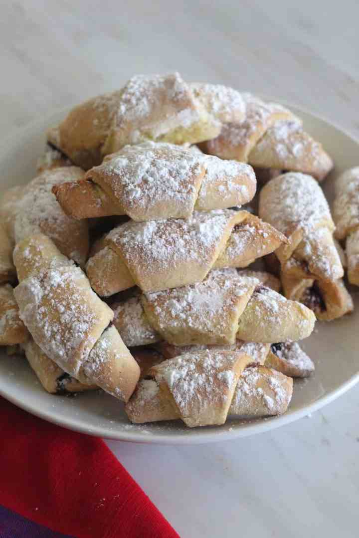 A plate with lots of rolled up crescent shape cookies that seem filled with jam.