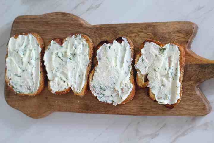 Layering crostini with ricotta, olive oil and dill mix. Picture shows a serving wood board with 4 crostini layered with ricotta.