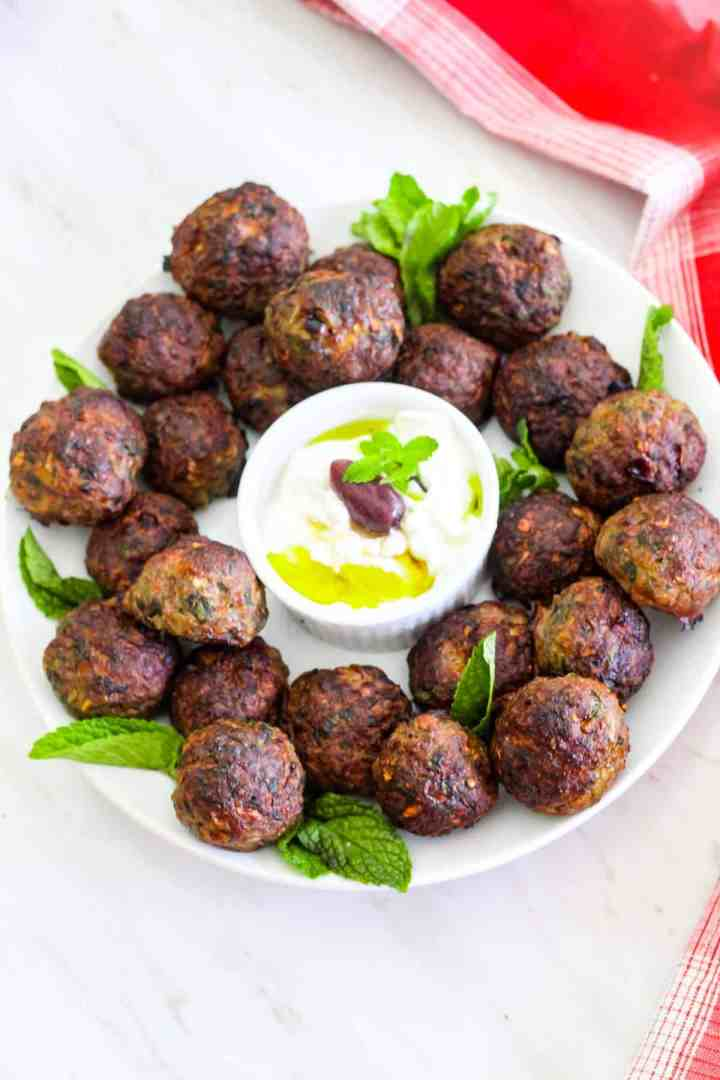 Albanian mint meatballs made with ground beef. These meatballs are called qofte and you see them served in a round platter garnished with fresh mint and a yogurt based dip.