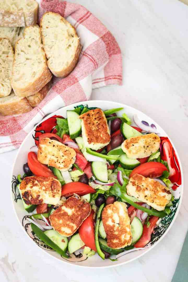 A platter of big family style salad topped with fried halloumi cheese shown next to a basket of fresh bread.