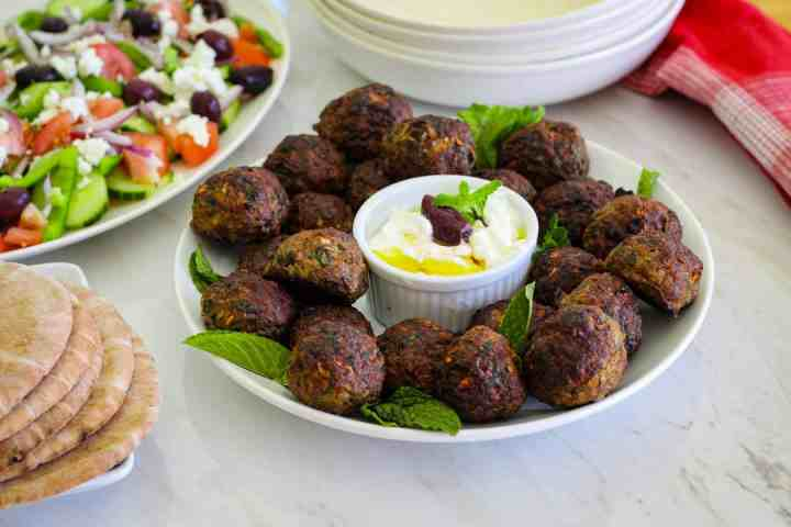 Baked Mint Meatballs (qofte) shown next to a big salad and pita bread, plus some serving platters in the background.