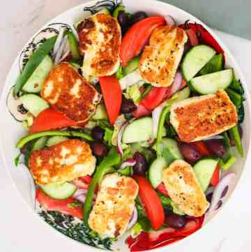 A round big salad platter with lots of veggies and fried halloumi cheese