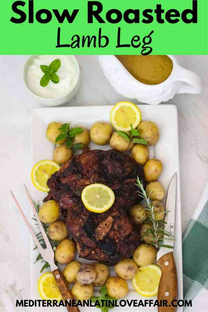 An image prepared for Pinterest. It shows the slow roasted lamb leg (boneless) served on a platter with potatoes, herbs and rosemary. Image has a title bar and the website link in the bottom.