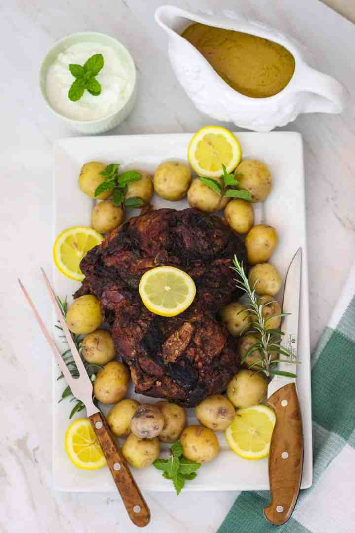 A platter with roasted lamb leg, potatoes, rosemary, lemon, cutting utensils, mint. Next to the platter there's a gravy jar and a yogurt dip.