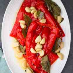 An oval platter with red peppers, garlic, bay leaves, peppercorn etc