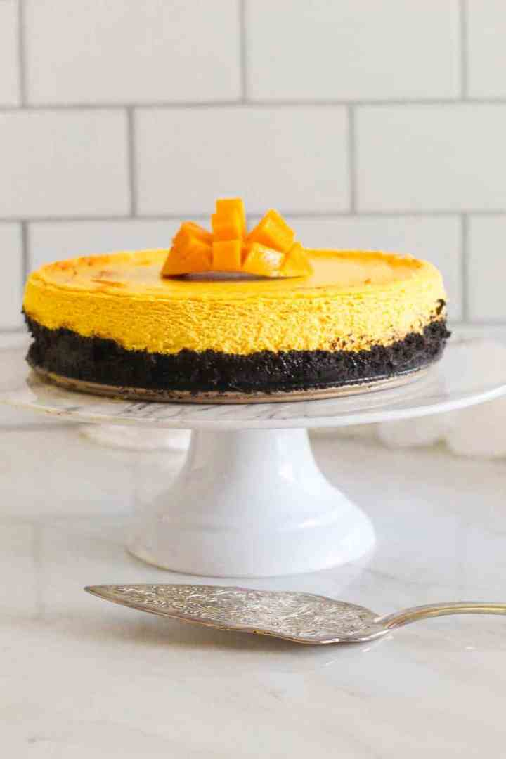 Mango cheesecake with oreo crust on a white cake display. There's freshly cut mango over the cheesecake and a cutting utensil nearby.