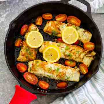 Cast Iron cooked halibut shown right after cooking. Skillet is shown with 4 halibut fillets, garnished with lemon slices, diill and cherry tomatoes.
