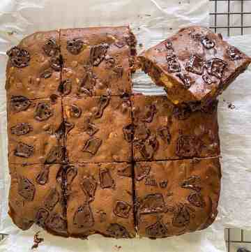 Picture shows just baked and cut brownies on a cooling rack. Brownies have been cut into a 9 pieces in a 3x3 format, one piece is slightly slanted so you can see the slice sideways.