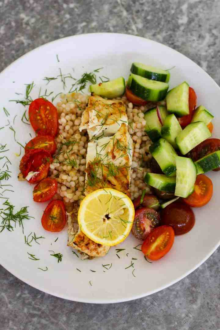 Plated halibut dinner with cast iron seared halibut, pearl couscous and salad. #halibut #dinner #seafood #mediterraneanlatinloveaffair