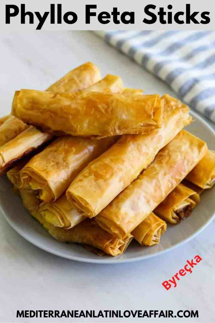 An image prepared for Pinterest. It shows the phyllo feta sticks on a serving platter piled up on top of each other. Then there's a title bar on top of the image and the website link in the bottom. #byrek #borek #burek #mediterraneanlatinloveaffair