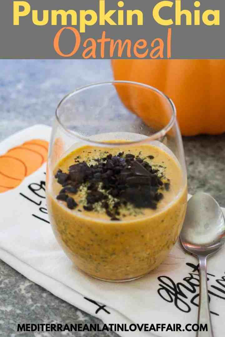 Pumpkin Chia Oatmeal topped with dark chocolate. Oatmeal is served over a clear glass placed on a towel, next to a spoon. Image has a title bar and the website link at the bottom.