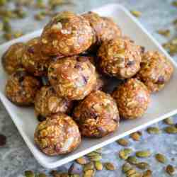 Pumpkin seeds energy bites, piled on a pyramid shape on a square serving dish.