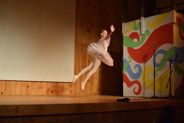 ballerina doing a grand jete across sstage