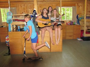 campers in their cabin singing and riding a scooter