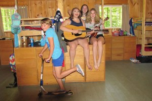 campers hanging out in teh cabin playing guitar and riding a scooter