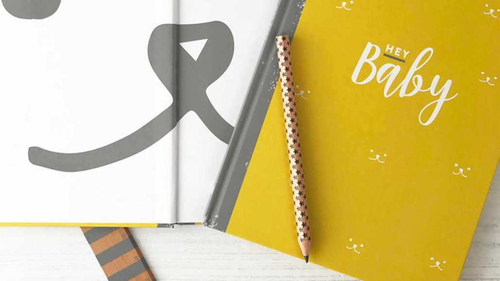 Hey Baby LGBTQ+ friendly baby memory book in yellow with a pencil lying on top.