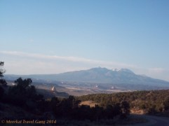 It's a weird sight - red sand and rock all around, but look up and see the snowy peaks of La Sal mountain.