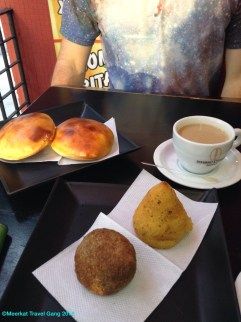 At the top are hamburginhos (a hamburger sandwich) and at the bottom is a coxinha (the pointy golden one) and kibe. Coxinha is shredded chicken & sauce, wrapped in some kind of mash/dough, and deep fried. Kibe is more Lebanese / Arabic.