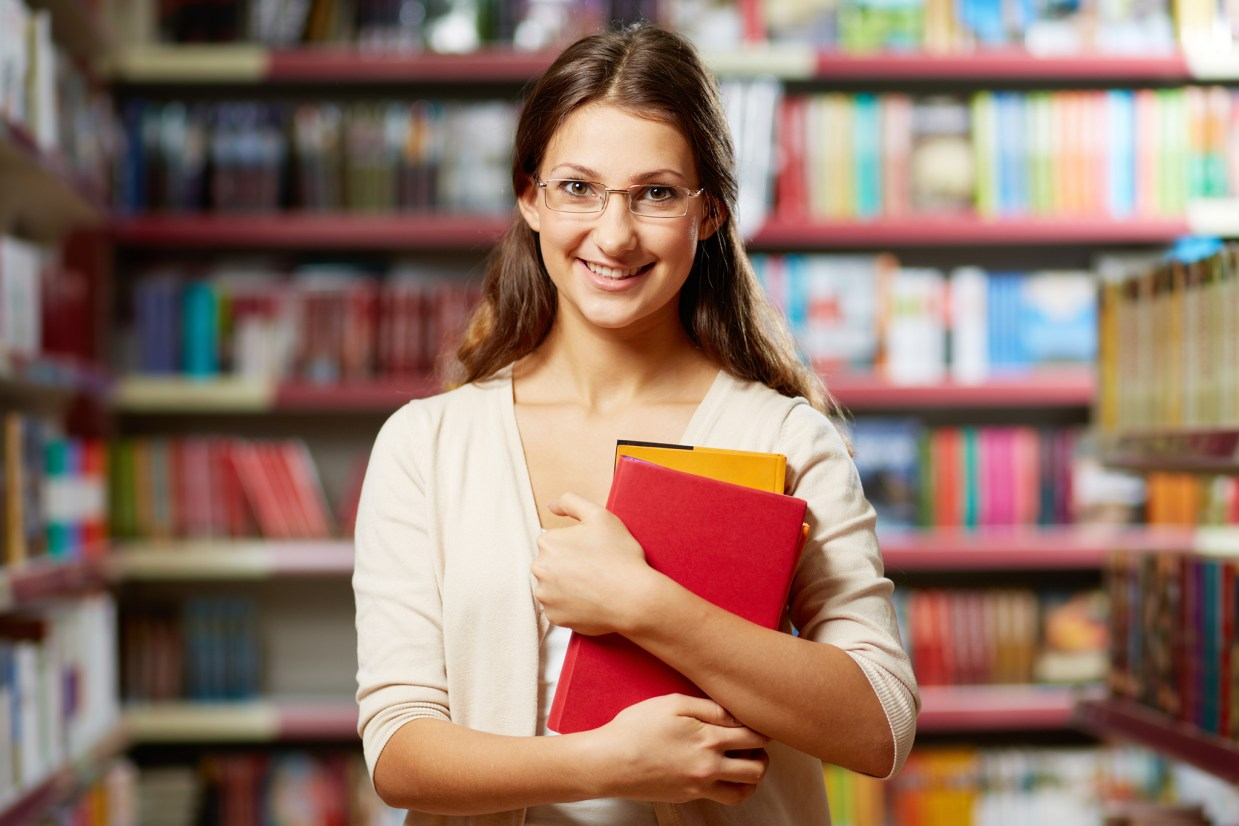 young woman smiling, holding library books