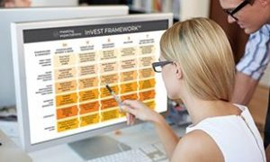 Image of girl pointing to InVEST Framework diagram on computer