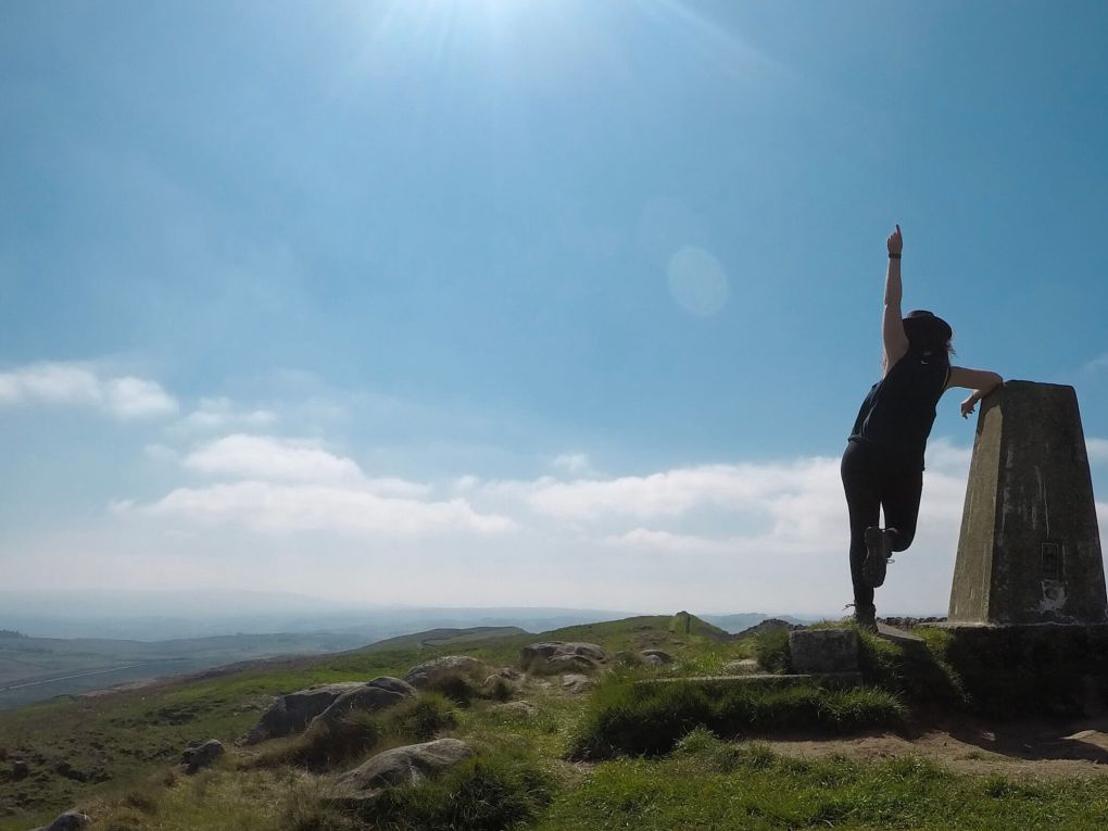 Standing at a trig point overlooking a valley and celebrating the fact i got up a massive hill