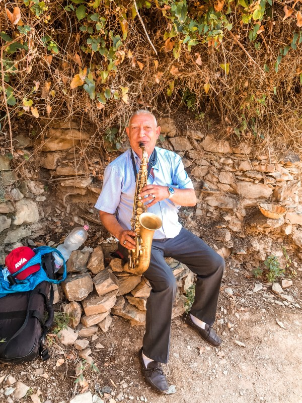 Elderly man plays saxophone on a hiking path in the middle of the cinque terre