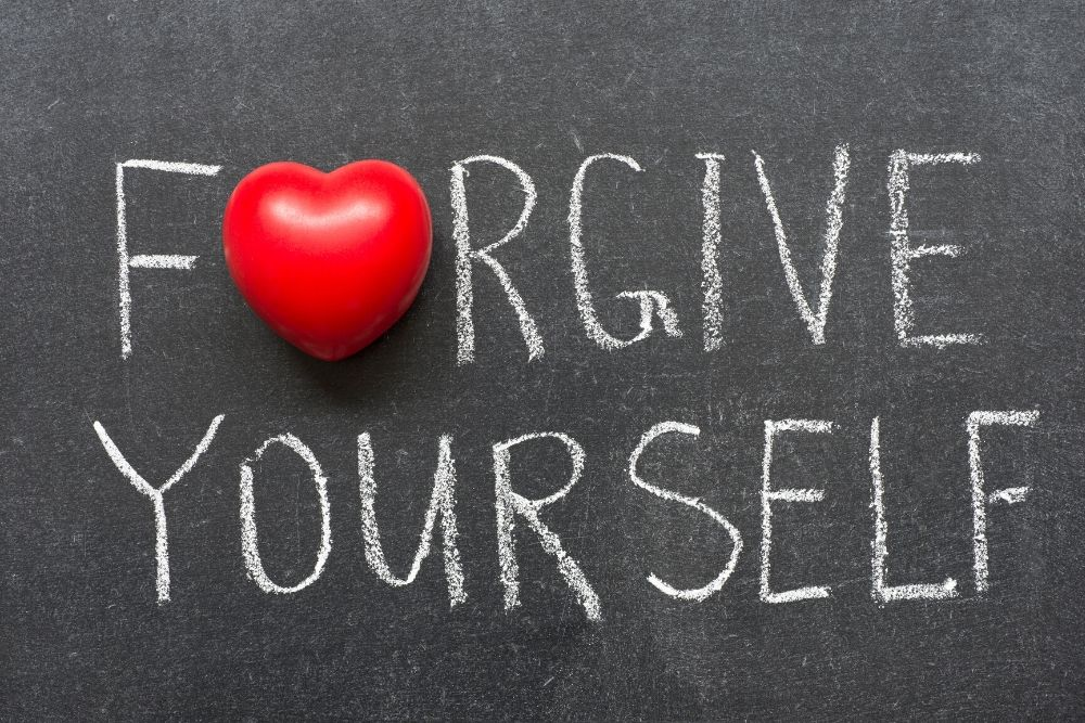 Forgive yourself is written on the chalkboard