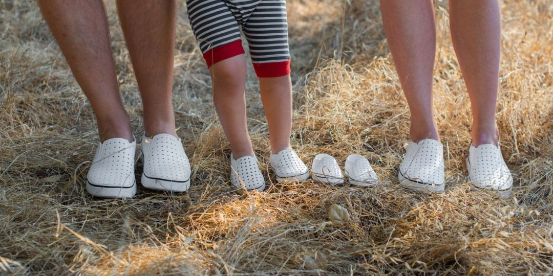 Photo of the shoes of a growing family with a pair waiting for their infant.