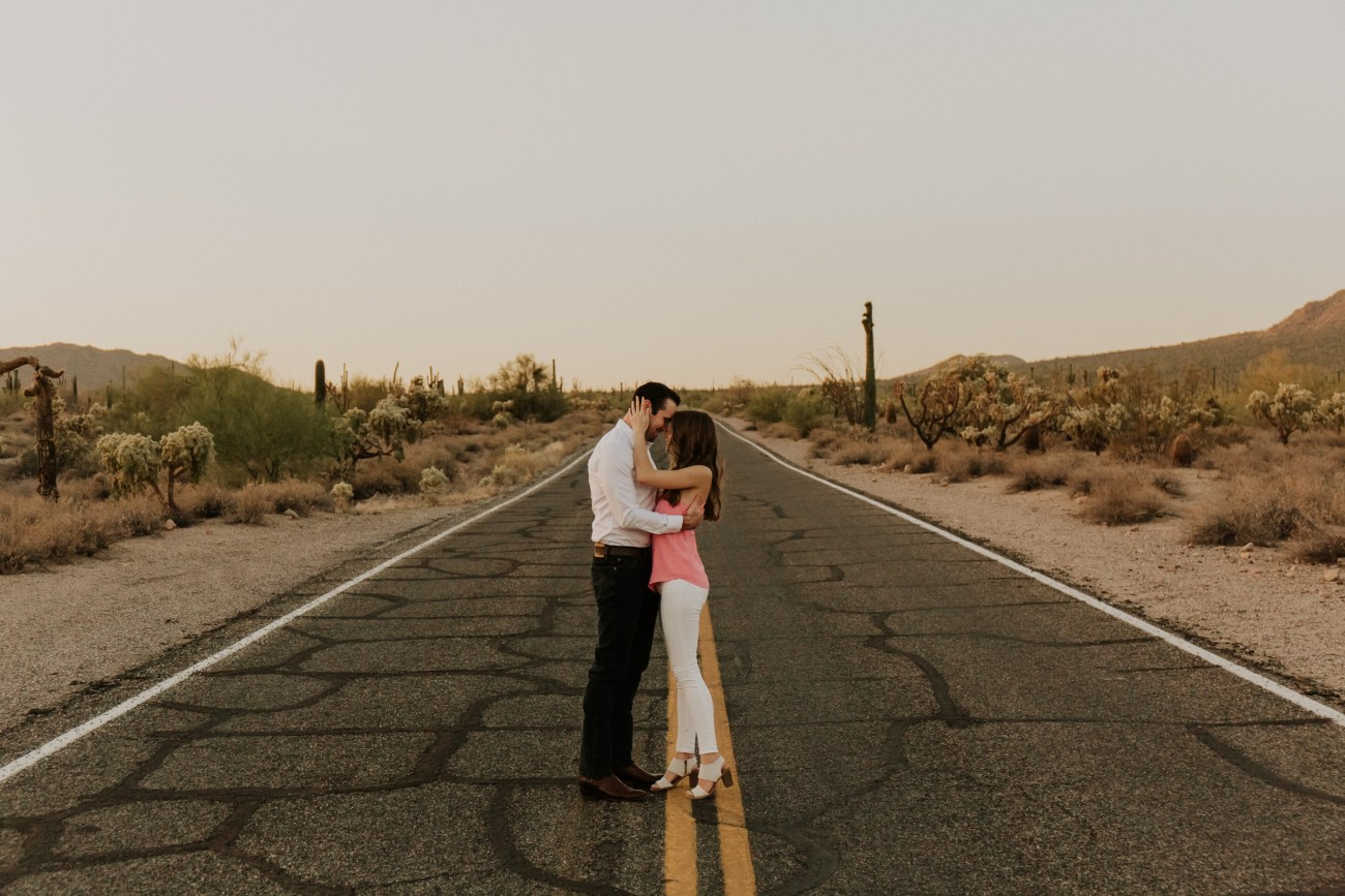 Megan Claire Photography | Arizona Wedding Photographer. Desert engagement photoshoot walking on road. @meganclairephoto