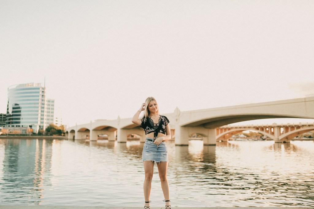 Megan Claire Photography | Arizona Portrait + Wedding Photographer. Urban lakeside portrait photoshoot session. Medium length blonde hair, denim skirt, black floral tie top.