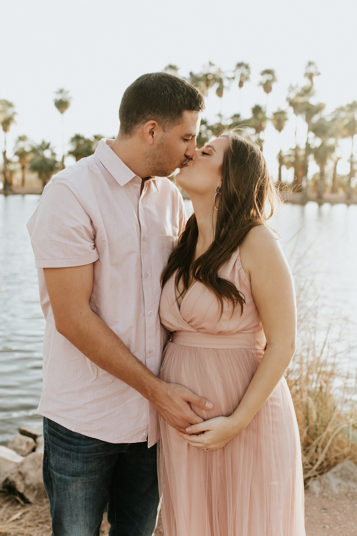 Megan Claire Photography | Phoenix Arizona Maternity Photographer. Arizona maternity photoshoot surrounded by palm trees, desert, and water. Pink maternity dress, white sheer maternity dress @meganclairephoto