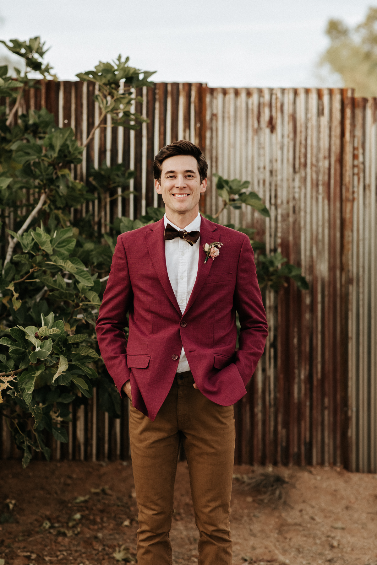 Megan Claire Photography | Arizona Wedding Photographer.  Rustic Glam Backyard Wedding. Groom wearing maroon red suit with bow tie