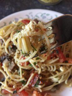 Fresh Vegan Spaghettini twirled on a fork, sprinkled with cashew parmesan cheese